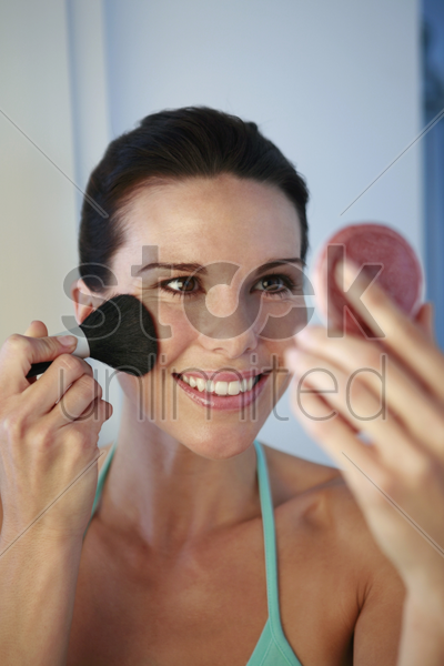 woman applying blusher stock photo