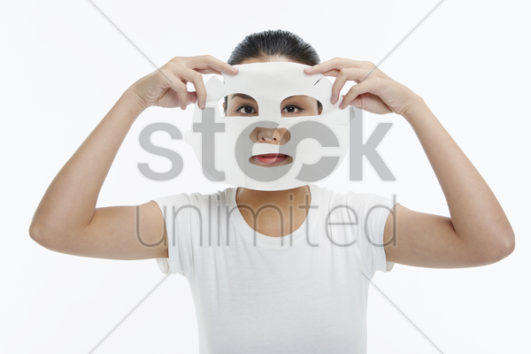 woman applying face mask stock photo