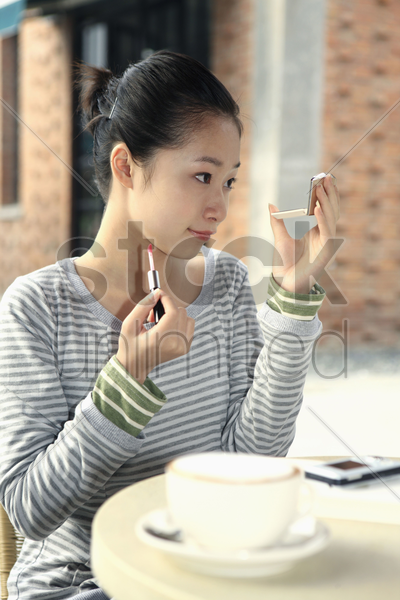 woman applying lip gloss while looking at compact mirror stock photo