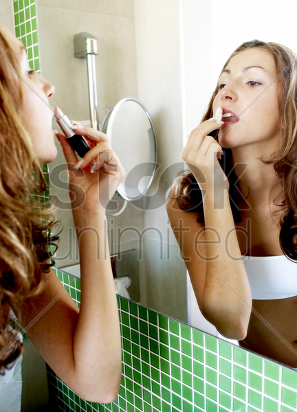woman applying lipstick in the bathroom stock photo