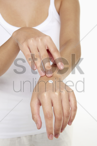 woman applying lotion on her hand stock photo