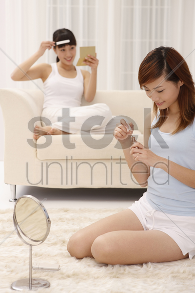 woman applying nail polish, another woman combing her fringe in the background stock photo