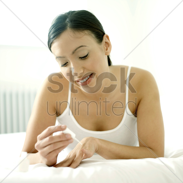 woman applying nail polish on her finger nails stock photo