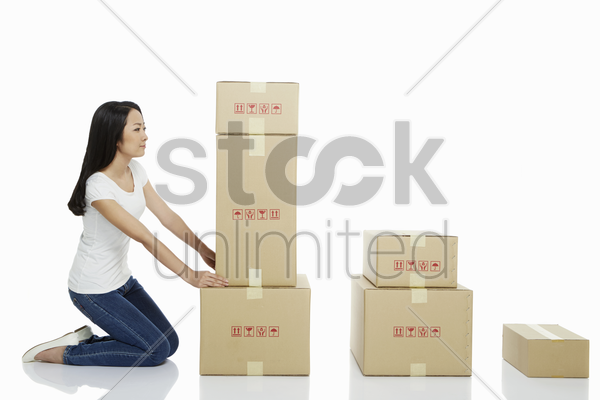 woman arranging a stack of cardboard boxes stock photo