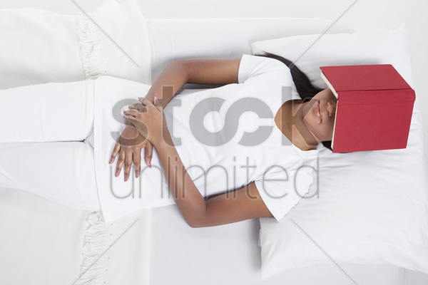 woman asleep with book covering her face stock photo