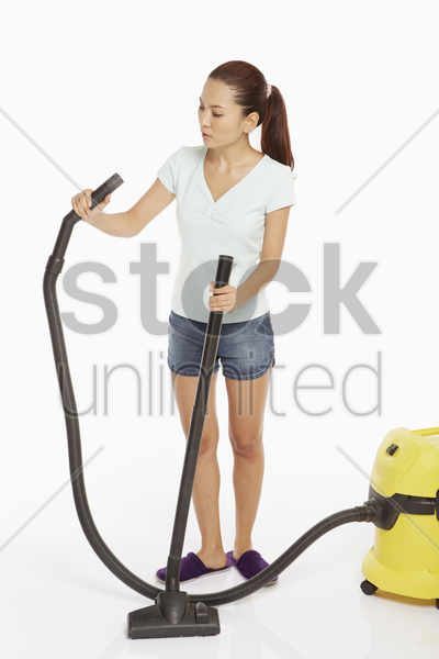 woman attaching the grip of a vacuum cleaner stock photo