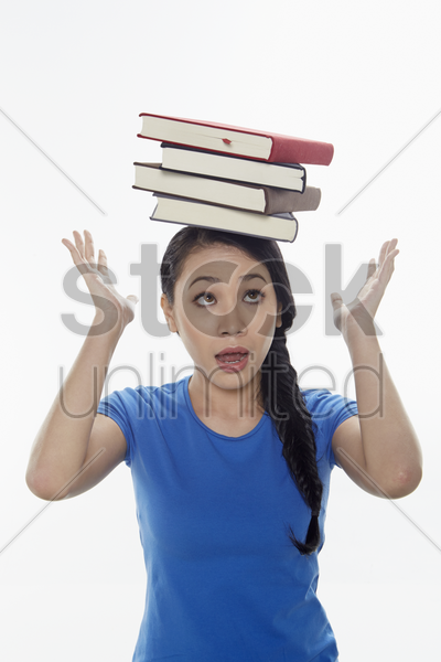 woman balancing books on her head stock photo