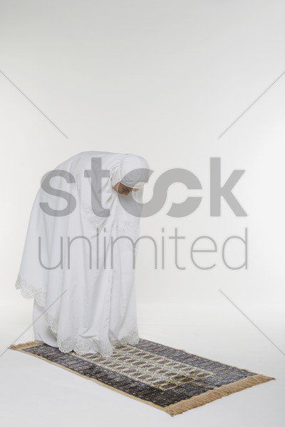 woman bending at her waist until palms reach her knees and staying still stock photo