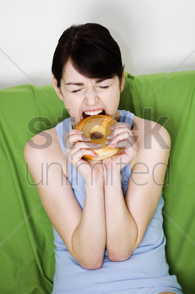 woman biting on a doughnut stock photo