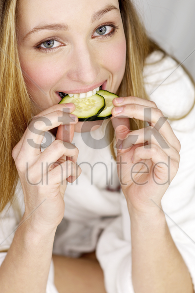 woman biting two slices of cucumber stock photo