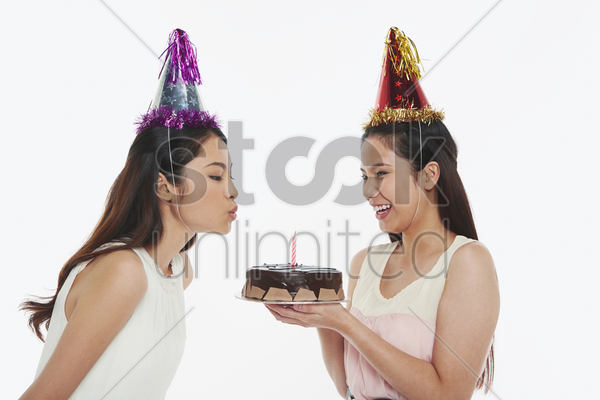 woman blowing a candle on birthday cake stock photo
