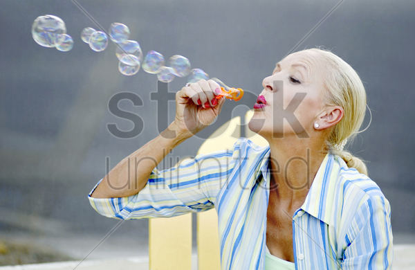 woman blowing soap bubbles stock photo
