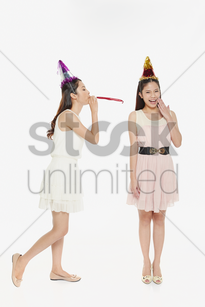 woman blowing the party horn blower at her friend stock photo