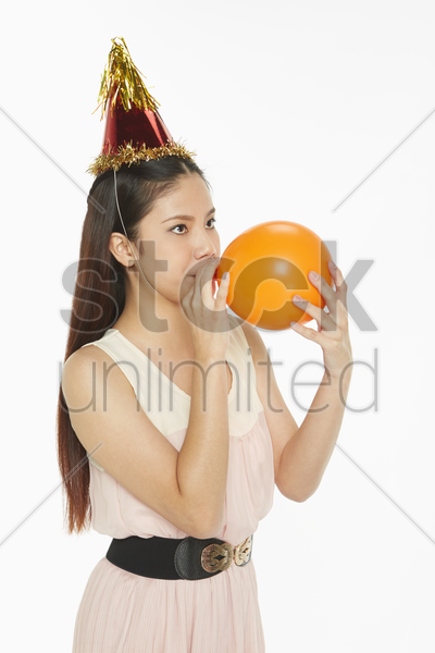 woman blowing up a balloon stock photo