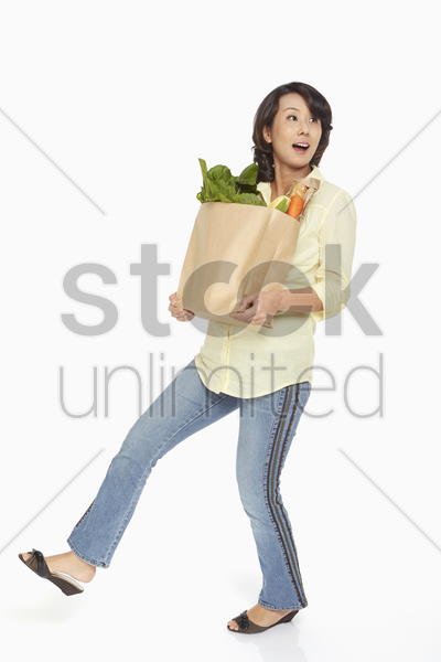 woman carrying a bag of groceries stock photo