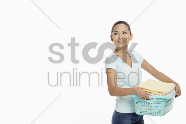 woman carrying a basket of clean laundry stock photo