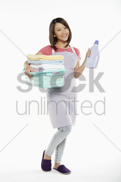 woman carrying a bottle of detergent and towels stock photo