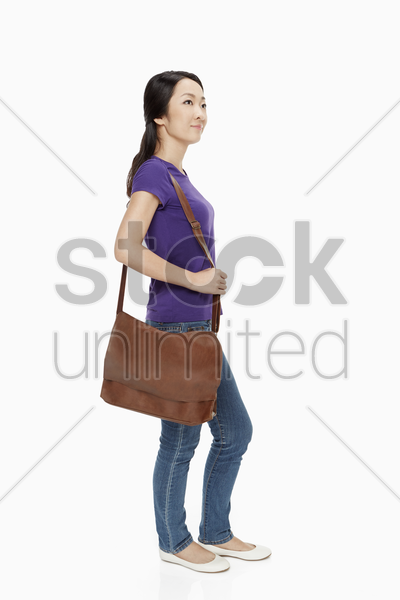 woman carrying a brown sling bag stock photo