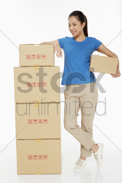 woman carrying a cardboard box stock photo