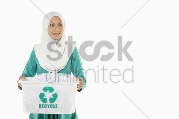 woman carrying a plastic box filled with shredded paper stock photo