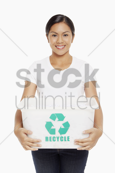 woman carrying a plastic box with a recycle logo on it stock photo