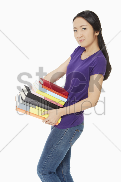 woman carrying a stack of books stock photo