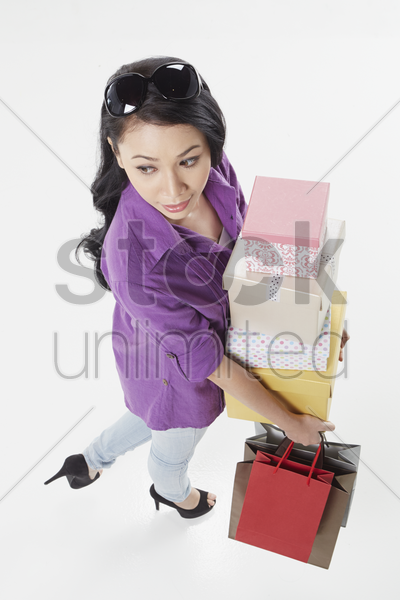 woman carrying a stack of boxes and shopping bags stock photo