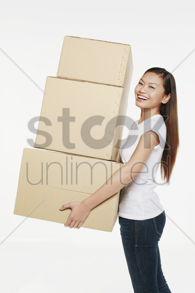 woman carrying a stack of boxes stock photo