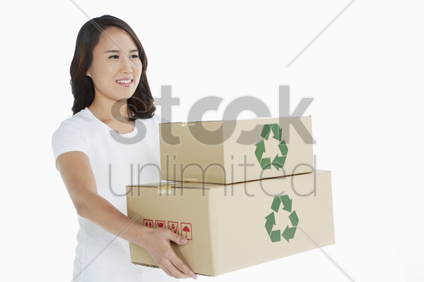 woman carrying a stack of cardboard boxes stock photo