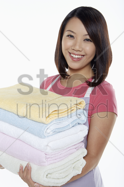 woman carrying a stack of clean towels stock photo