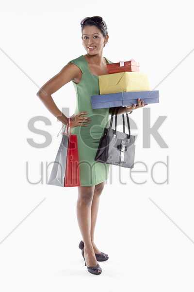 woman carrying a stack of gift boxes and shopping bags stock photo