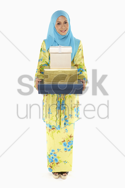 woman carrying a stack of gift boxes stock photo