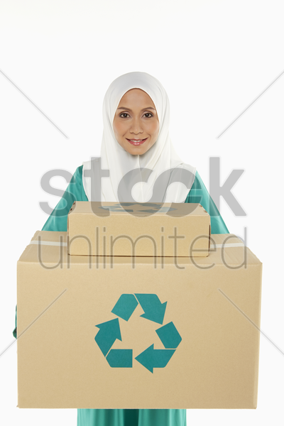 woman carrying a stack of recyclable cardboard boxes stock photo