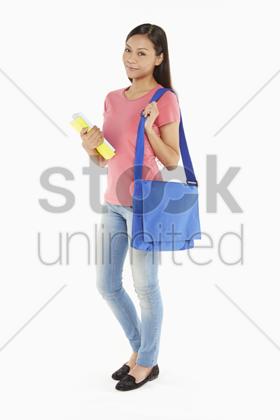 woman carrying books and a sling bag stock photo