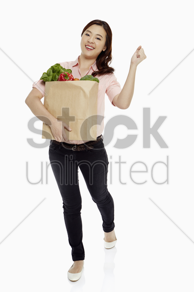 woman carrying groceries, cheering stock photo