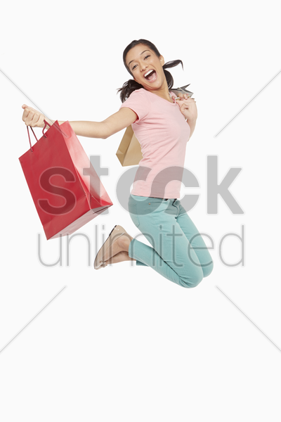 woman carrying shopping bags, jumping mid air stock photo