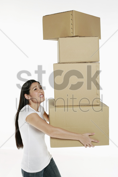 woman carrying stack of boxes stock photo