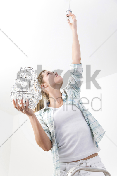 woman changing the light bulb stock photo