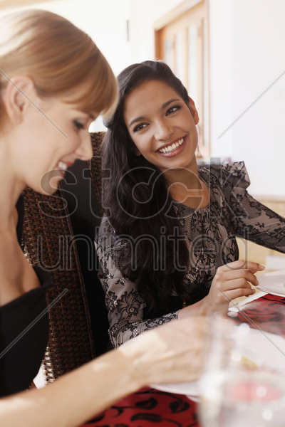 woman chatting while eating together stock photo
