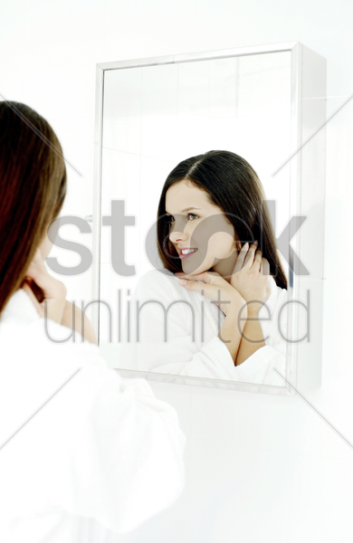 woman checking her face in the mirror stock photo