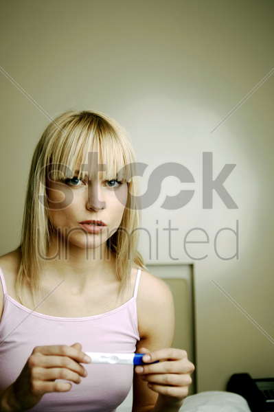 woman checking her pregnancy test result stock photo