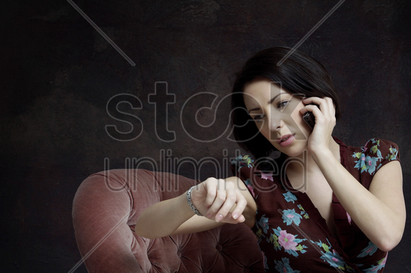 woman checking her watch while talking on the phone stock photo