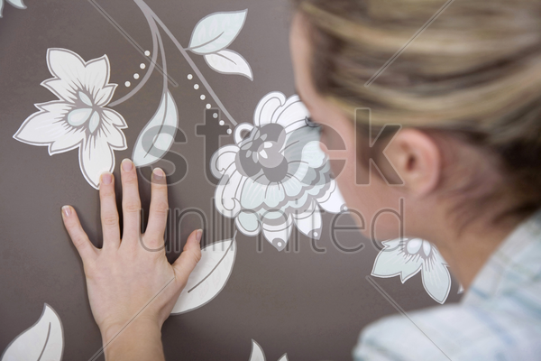 woman checking wallpaper's texture stock photo