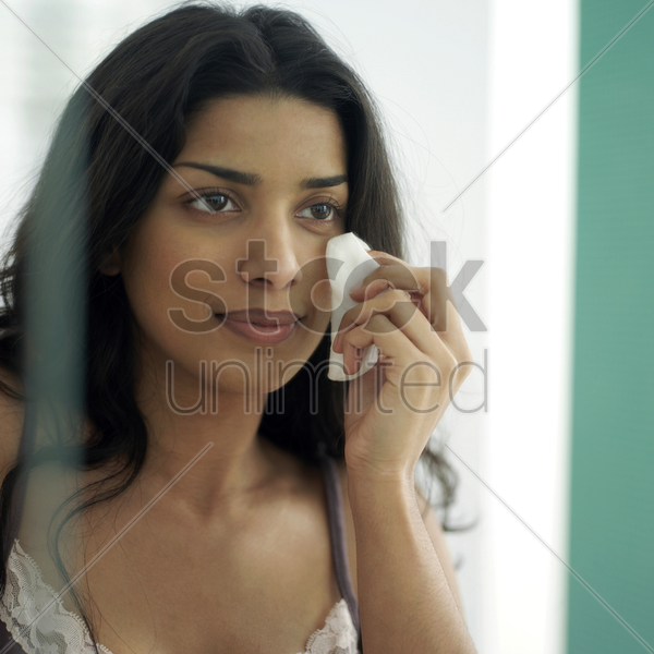 woman cleaning her face with a cotton stock photo