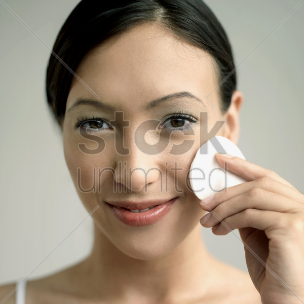 woman cleaning her face with cotton stock photo