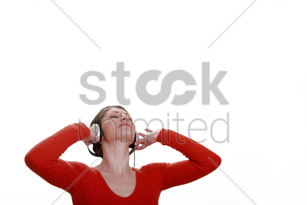 woman closing her eyes while listening to music on the headphones stock photo