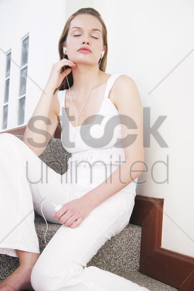 woman closing her eyes while listening to music on the mp3 player stock photo