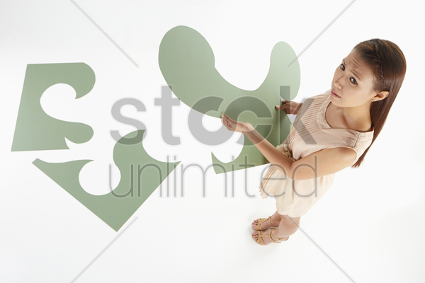 woman contemplating while solving puzzle stock photo