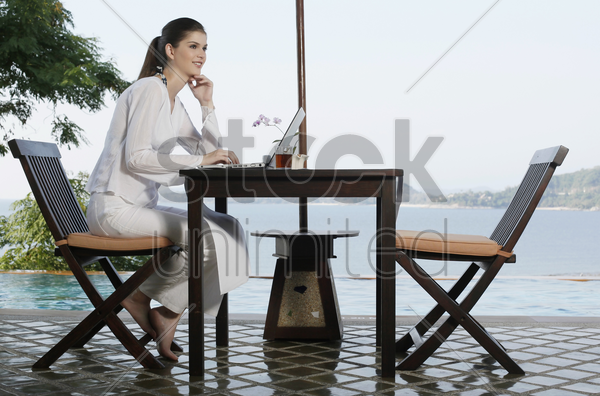 woman contemplating while using laptop stock photo