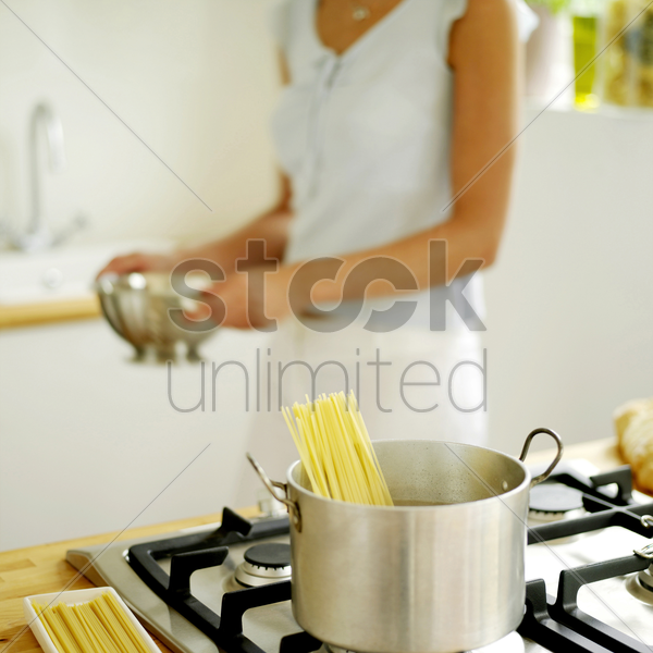 woman cooking spaghetti at home stock photo
